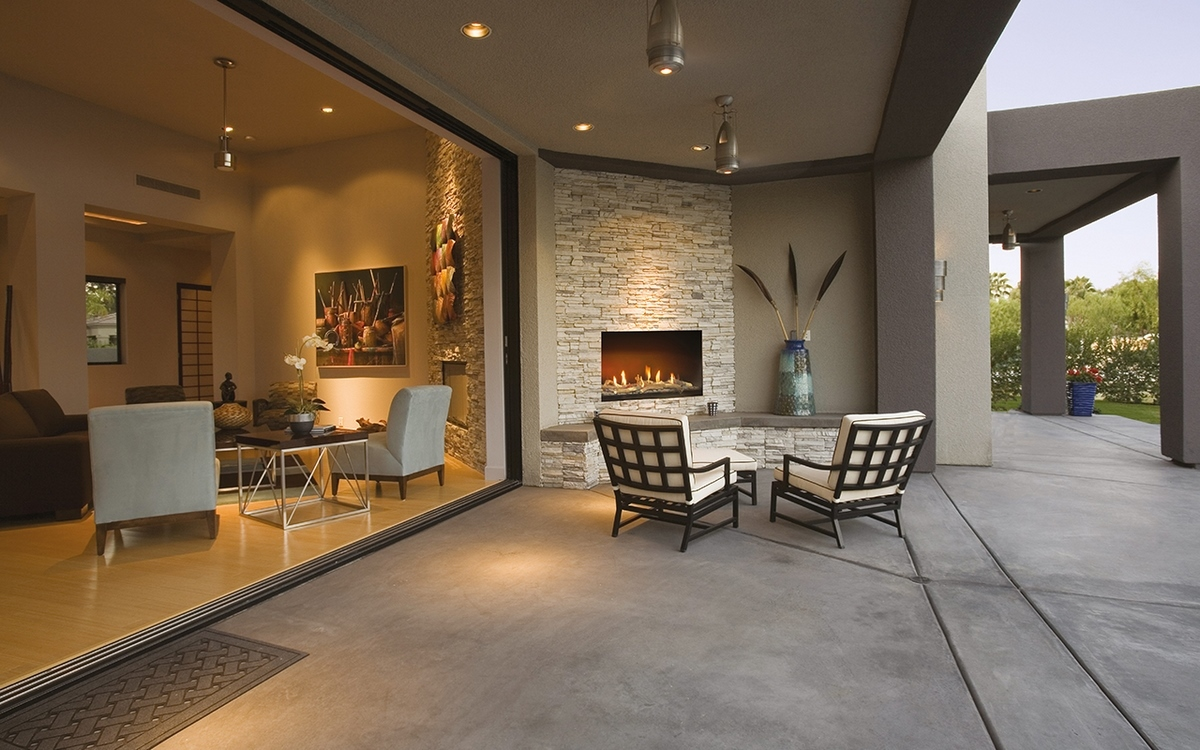 View of chairs by fireplace in patio of a modern home